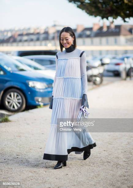 Aimee Songwearing blue white checked dress silver JW Anderson bag is seen outside Loewe during Paris Fashion Week Spring/Summer 2018 on September 29...