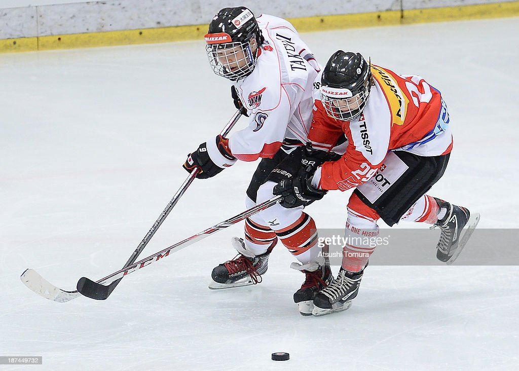 Aina Takeuchi (L) of Japan and Romy Eggimann (R) of Switzerland battles for the pack in the match between Japan and Switzerland during day three of the Ice Hockey Women's 5 Nations Tournament at the Shin Yokohama Skate Center on November 9, 2013 in Yokohama, Japan.