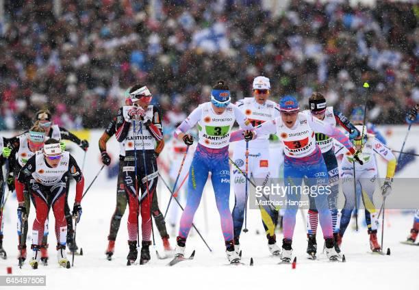 Aino Kaisa Saarinen of Finland hands over to team mate Kerttu Niskanen in the Men's and Women's Cross Country Team Sprint Final during the FIS Nordic...