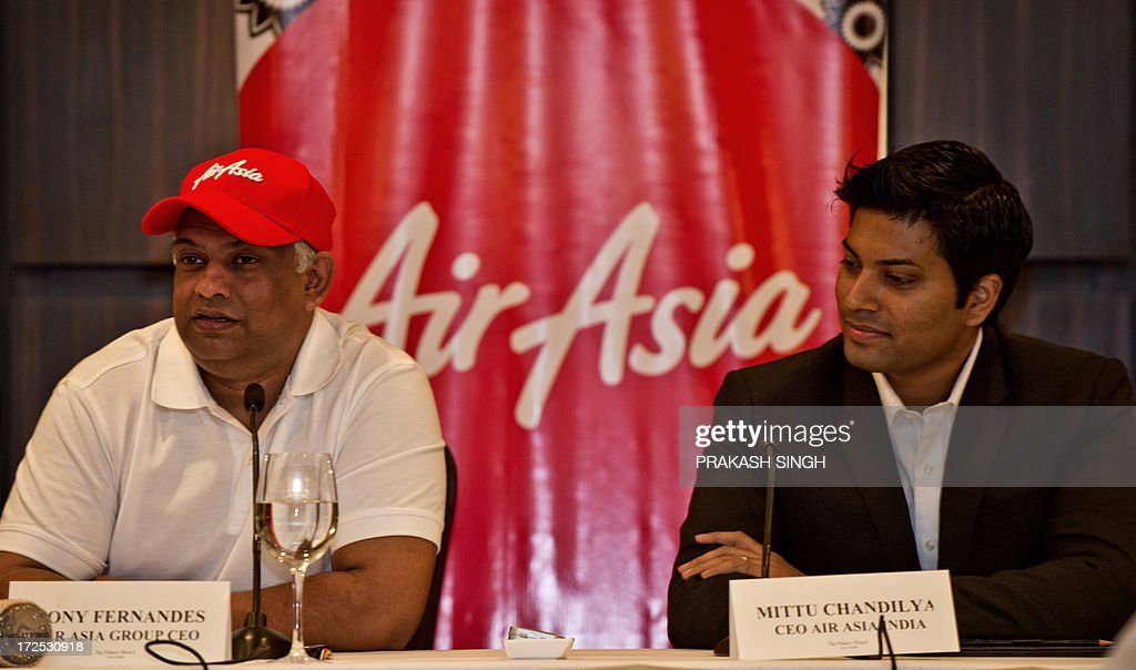 Air Asia CEO Tony Fernandes (L) addresses the media as Air Asia India CEO Mitu Chandilya looks on during a press conference in New Delhi on July 3, 2013. Over four months ago the Foreign Investment Promotion Board (FIPB) cleared a proposal for the setting up of a newairline, AirAsia India, by Malaysian carrier AirAsia which has joined hands with the Tata Group and Arun Bhatia of Telestra. AFP PHOTO/ Prakash SINGH