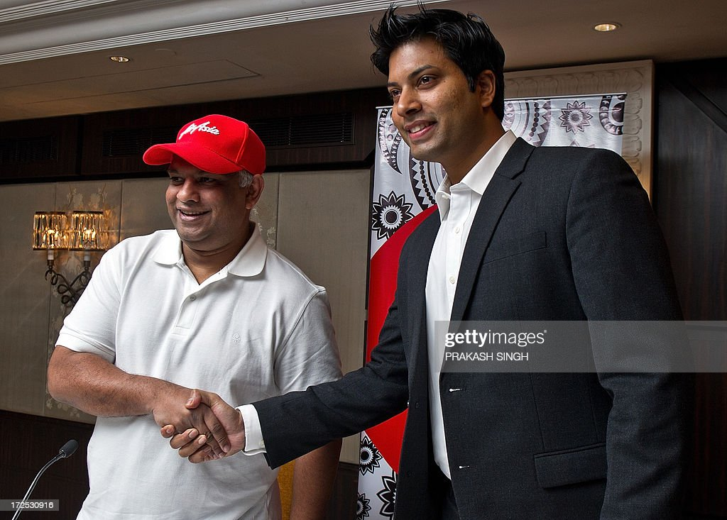 Air Asia CEO Tony Fernandes (L) shakes hands with Air Asia India CEO Mitu Chandilya during a press conference in New Delhi on July 3, 2013. Over four months ago the Foreign Investment Promotion Board (FIPB) cleared a proposal for the setting up of a newairline, AirAsia India, by Malaysian carrier AirAsia which has joined hands with the Tata Group and Arun Bhatia of Telestra. AFP PHOTO/ Prakash SINGH