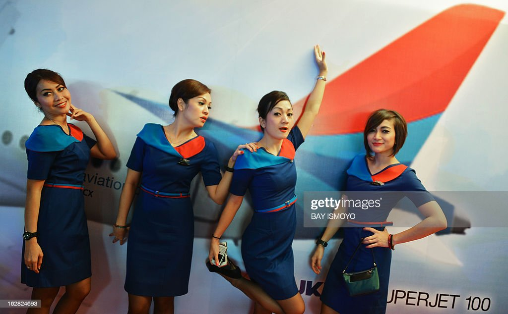 Air attendants of Sky aviation pose for photos in front of a poster of the airline company's new aircraft the Sukhoi Superjet 100 during the...