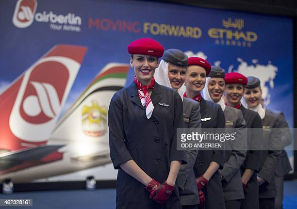 Air Berlin and Etihad airways hostesses pose prior to CEOs of Etihad and Air Berlin press conference in hangar 15 at the airport in Schoenefeld on...