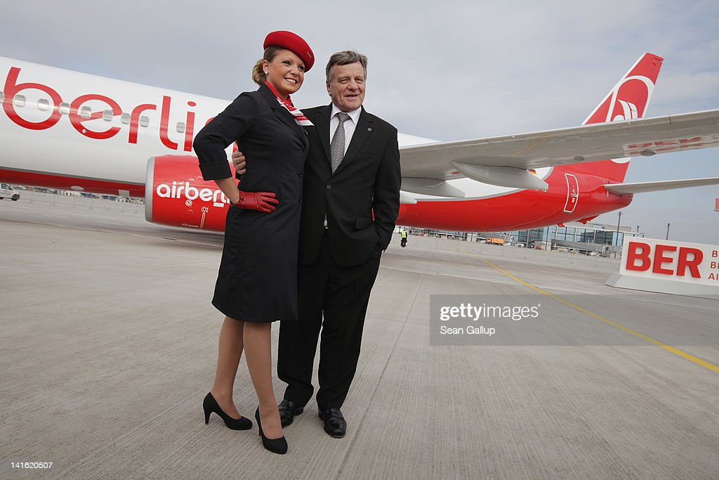 Air Berlin CEO Hartmut Mehdorn poses with an Air Berlin stewardess next to an Air Berlin passenger plane after he signed a document confirming Air Berlin's acceptance into the oneworld alliance at Berlin Brandenburg Airport on March 20, 2012 in Berlin, Germany. Air Berlin joins 10 other international airlines in the alliance.