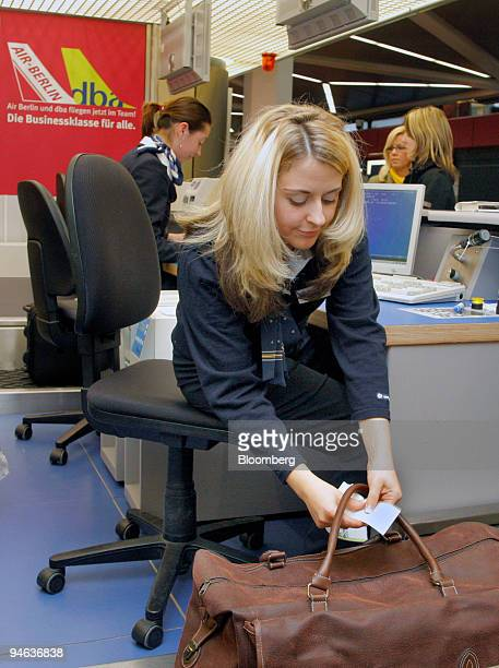 Air Berlin employee Christinane Dennig attaches badges to bags at the Air Berlin luggage belt at the BerlinTegel airport Germany on Thursday December...