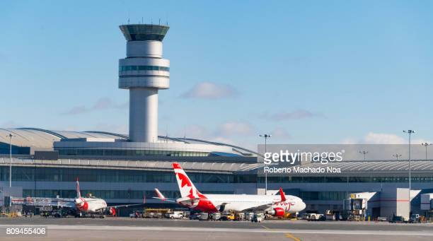 Air Canada Rouge tourist plane and control tower in Pearson International airport Red and white passenger airplanes getting loaded and serviced