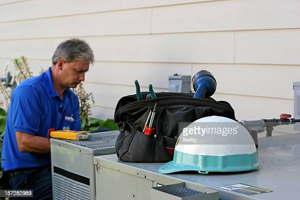 Air conditioner repairman working on an outdoor unit