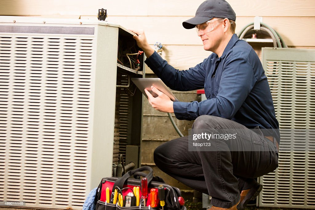 Air conditioner repairman works on home unit. Blue collar worker. : Stock Photo