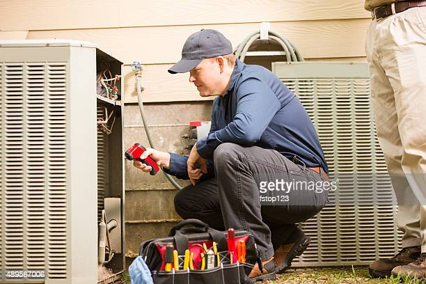 Air conditioner repairmen work on home unit. Blue collar workers.