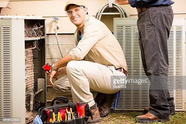 Acondicionador de aire repairmen trabajo en casa unidad. Anillo azul de los trabajadores.