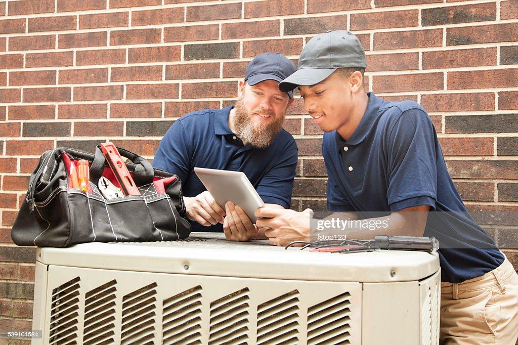 Air conditioner repairmen work on home unit.  Digital tablet. : Stock Photo