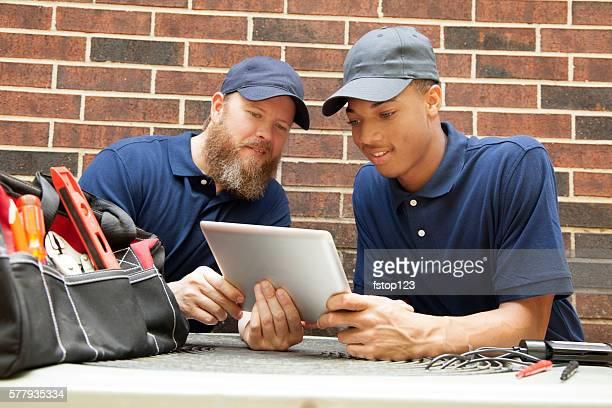 Air conditioner repairmen work on home unit.  Digital tablet.