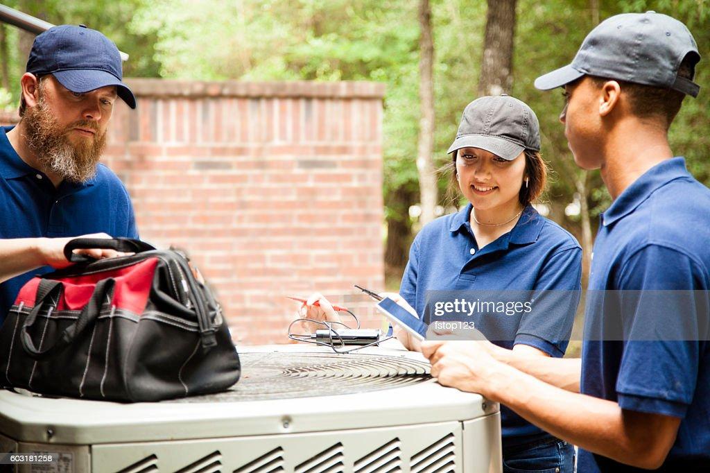 Air conditioner repairmen work on home unit. : Stock Photo