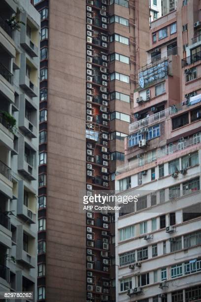 Air conditioning units are seen on the facade of highrise residential buildings in Hong Kong's MidLevels district on August 11 2017 Calls to restrict...