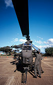 Air crewmen secure an AH-1 Cobra attack helicopter.