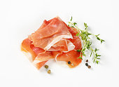 slices of air dried ham with thyme and pepper on white background
