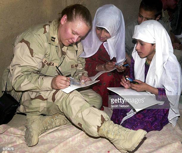 S Air Force Cpt Krista D'Andrea spells out her name for Afghan schoolgirls after handing out school supplies July 10 2002 at the Charikar Childrens...