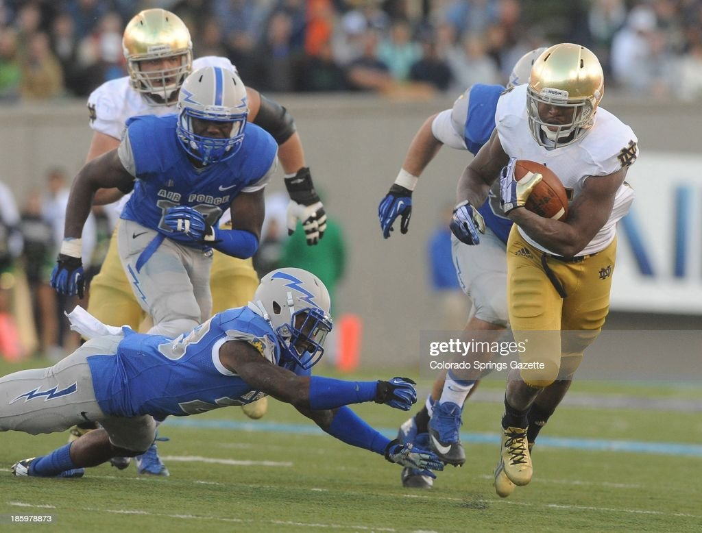 Air Force defensive back Steffon Batts, bottom left, and linebacker Reggie Barnes, top left, chase Notre Dame running back Tarean Folston during the second half at Falcon Stadium in Colorado Springs, Colorado, on Saturday, October 26, 2013. Notre Dame won, 45-10.