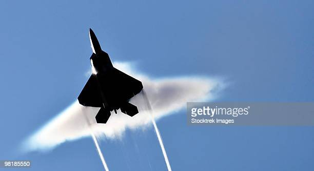 A U.S. Air Force F-22 Raptor aircraft executing a supersonic flyby.