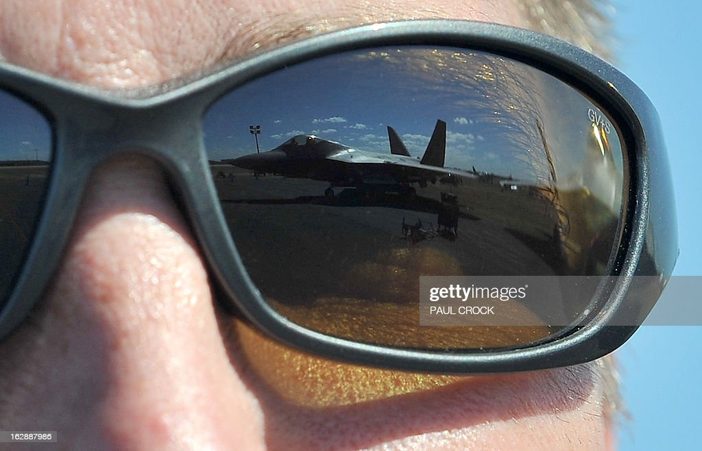 Air Force F-22 Raptor is reflected in the sunglasses of Lt Col Jeff Hawkins of the 94th Fighter Squadron during the Australian International Airshow in Melbourne on March 1, 2013. 180,000 patrons are expected through the gates over the duration of the event staged at the Avalon Airfield some 80kms south-west of Melbourne. AFP PHOTO / Paul CROCK