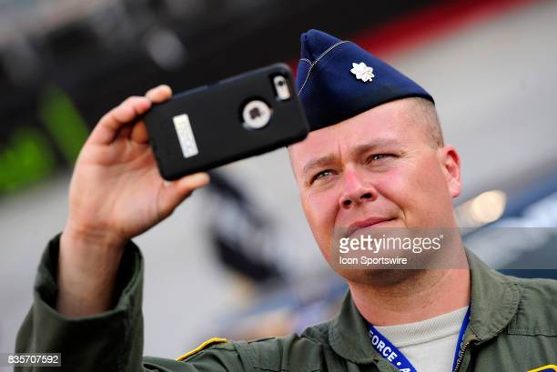 Air Force Lieutenant Colonel Terry Holmes records the prerace festivities on his iPhone before the start of the Bass Pro Shops NRA Night Race on...