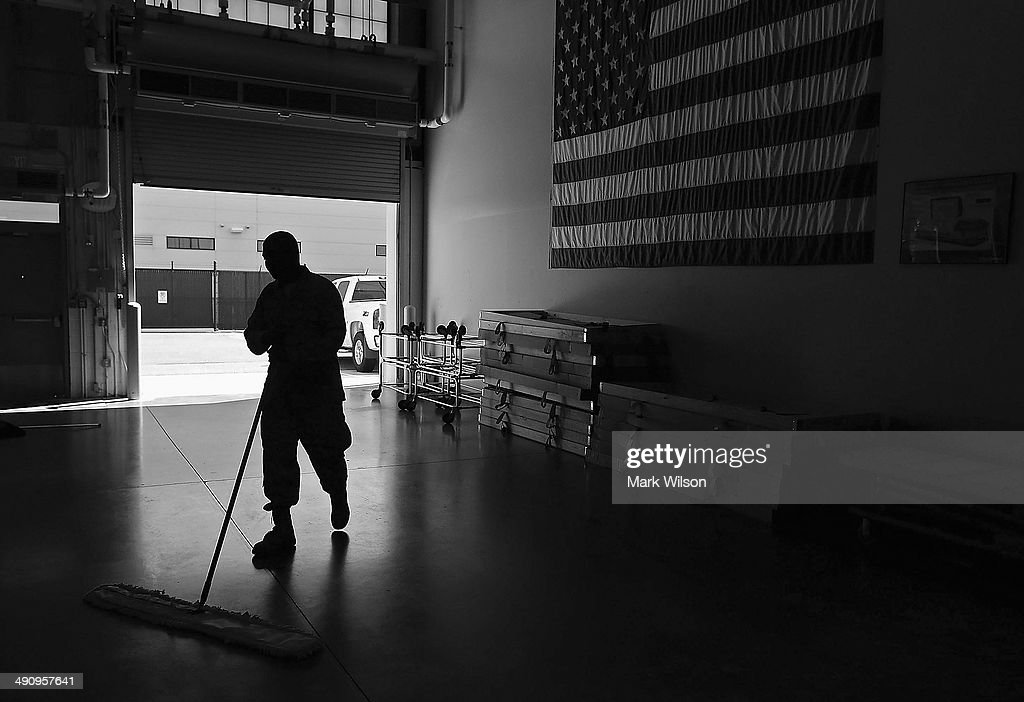 U.S. Air Force Mortuary Technician Senior Airman Joshua Solomon (R), sweeps the floor in the Departure Section of Dover Air Force Base Mortuary Affairs operations complex, June 21, 2013 in Dover, Delaware. Since the 1950s fallen members of the military fighting in conflicts aboard are brought to Dover's Air Force Mortuary Affairs operations complex which is the Defense Departments largest joint service mortuary facility in the United States.