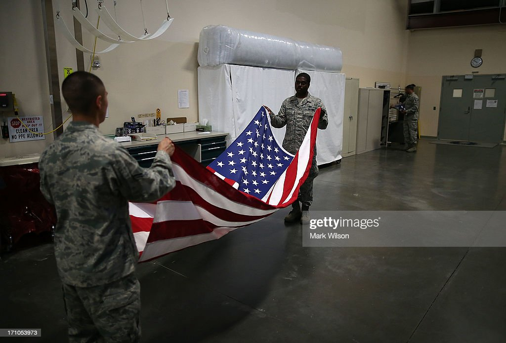 U.S. Air Force Mortuary Technicians Airman 1st. Class Cody Rodriguez (L) and Senior Airman Joshua Solomon (R), fold a flag in the Departure Section of Dover Air Force Base Mortuary Affairs operations complex, June 21, 2013 in Dover, Delaware. Since the 1950s fallen members of the military fighting in conflicts aboard are brought to Dover's Air Force Mortuary Affairs operations complex which is the Defense Departments largest joint service mortuary facility in the United States.