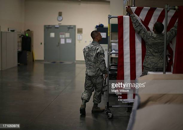 S Air Force Mortuary Technicians Airman 1st Class Cody Rodriguez and Senior Airman Joshua Solomon hang a flag in the Departure Section of Dover Air...