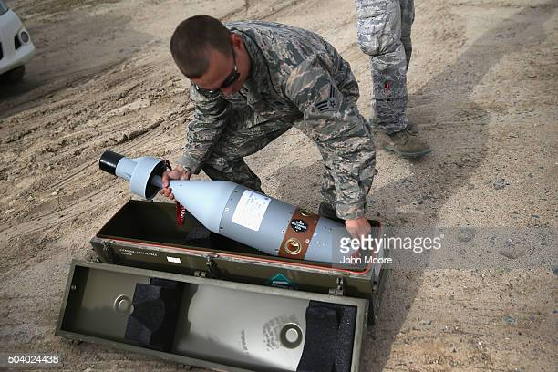 S Air Force munitions team member uncases the laserguided tip for a 500 pound bomb to be loaded onto an unmanned aerial vehicle for airstrikes on...
