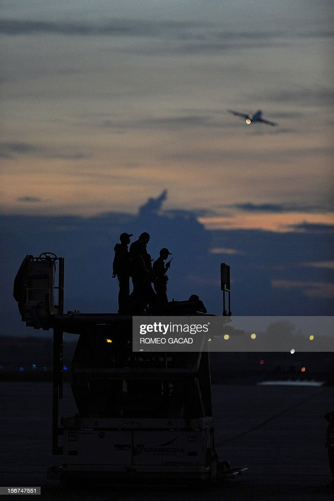Air Force One (top R, background), carrying US President Barack Obama, takes off from Phnom Penh airport as US security personnel keep watch on November 20, 2012. US President Barack Obama on Tuesday defied Chinese protests and raised concerns at a summit about territorial disputes that have sent diplomatic and trade shockwaves across the region. AFP PHOTO / ROMEO GACAD