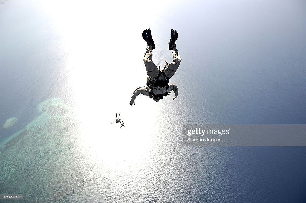 U.S. Air Force pararescuemen conducting a pararescue training jump from an HC-130 Hercules.
