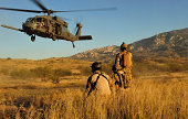 U.S. Air Force pararescuemen signal in a HH-60 Pave Hawk for extraction.
