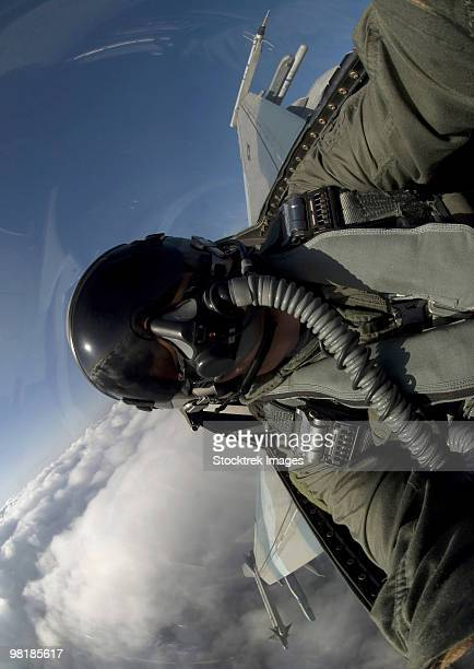 U.S. Air Force pilot turning sideways in an F-16 Fighting Falcon aircraft.