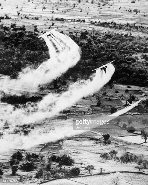 Air Force planes spray the Cambodian countryside with a herbicide probably Agent Orange to defoliate the area and expose Vietcong troops and...