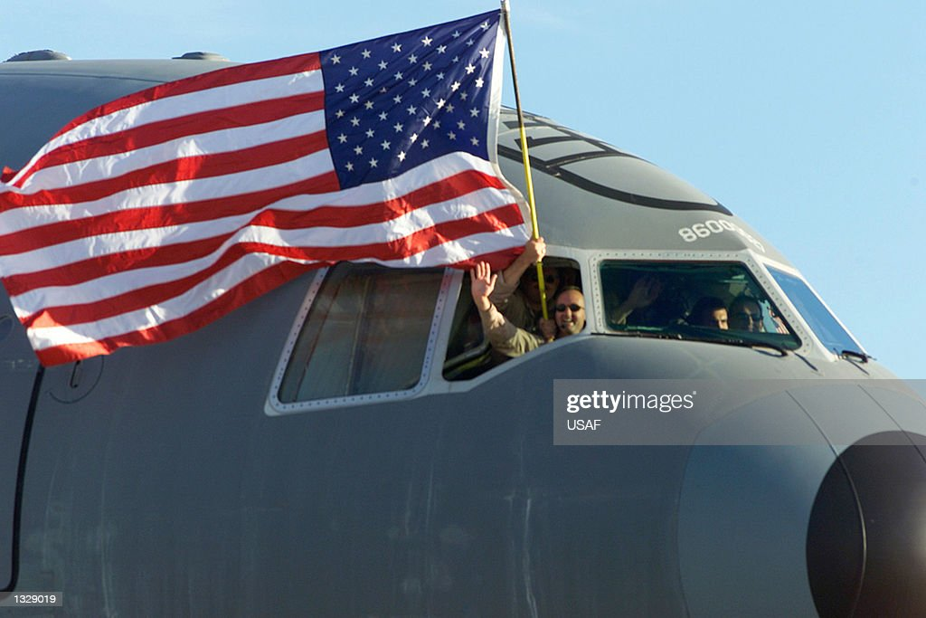 S Air Force reservists wave American flag from cockpit of a KC10a Extender as they return to McGuire Air Force Base October 19 2001 in NJ The...