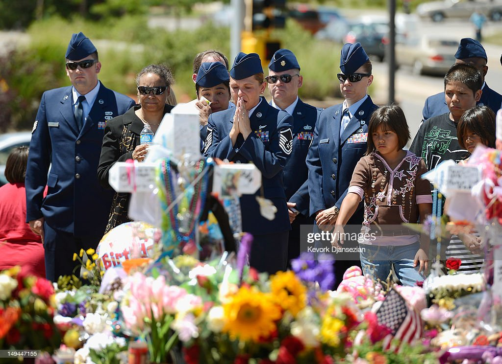 US Air Force Senior Master Sgt. Raea Thompson (C), from nearby Buckley Air Force base, prays as she and her fellow servicemen visit theater shooting victim Jesse Childress', a 29-year-old Air Force sergeant, roadside memorial set up across the street from Century 16 movie theater July 28, 2012 in Aurora, Colorado. Twenty-four-year-old James Holmes is suspected of killing 12 and injuring 58 others July 20 during a shooting rampage at a screening of 'The Dark Knight Rises' in Aurora, Colorado.