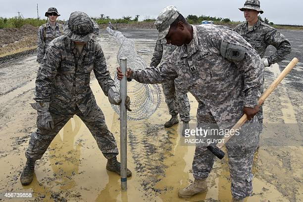 US air Force soldiers delimit with barbed wire the position of the next Ebola treatment center reserved for contaminated healthcare workers in...