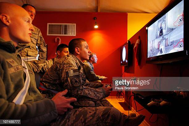 Air Force Staff Sargent Ryan Propst plays 'Call of Duty' video game with a small group of service members at the United Service members Organization...
