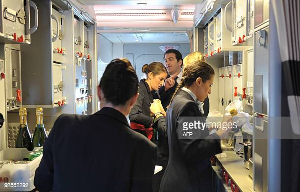 Air France crew members work in the cabin of the first Air France A380 during its flight from the Airbus plant in Hamburg to Paris' Roissy airport on...