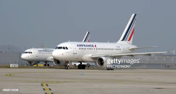 Air France planes movr on the tarmac at Roissy Charles de Gaulle airport near Paris on March 18 2015 AFP PHOTO ERIC PIERMONT