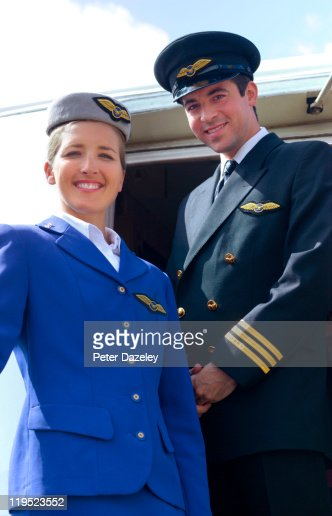 Air hostess and pilot on steps of airplane : Stock Photo