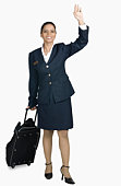 Air hostess carrying her luggage and smiling