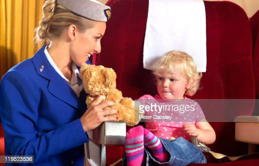 Air hostess entertaining child on airplane : Stock Photo