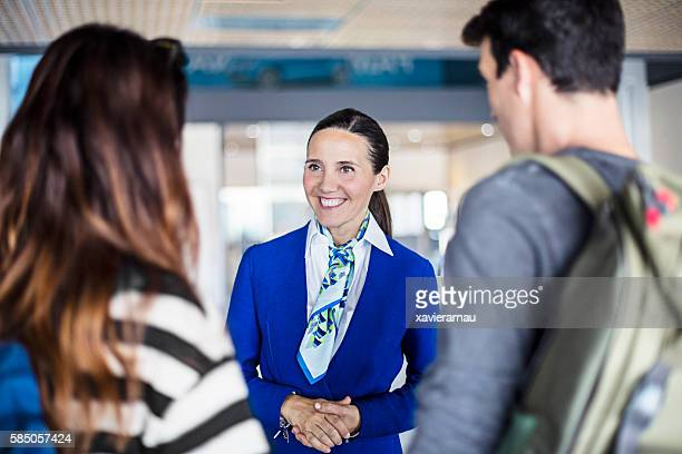 Air hostess helping young couple at airport