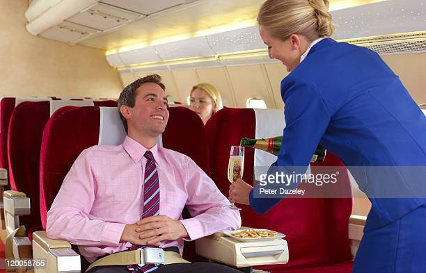 Air hostess pouring champagne in first class