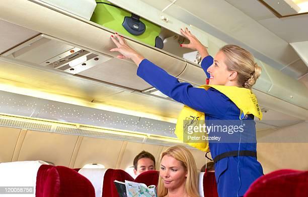Air hostess putting case in overhead locker