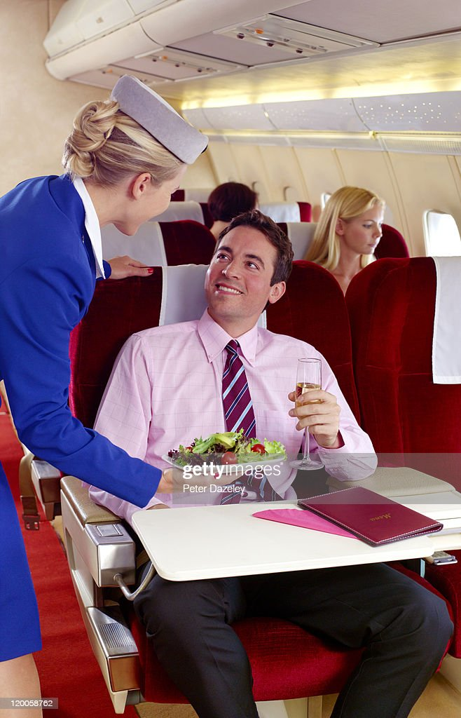 Air hostess serving food in first class : Stock Photo