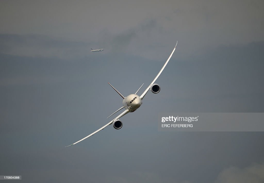 A Air India Boeing Dreamliner (C) flies over Le Bourget airport with an other jet in the background, near Paris on June 20, 2013 during the 50th International Paris Air show.