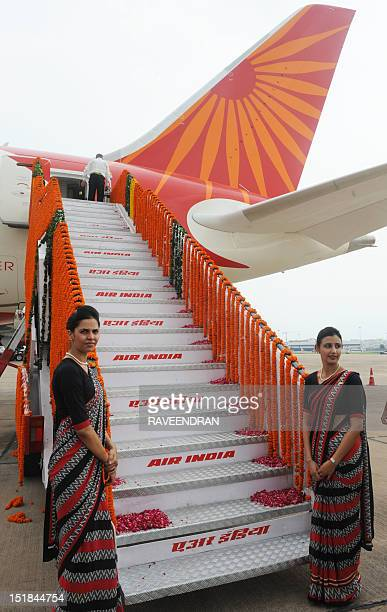 Air India flight attendants stand at the base of stairs during the unveiling of Air India's first Boeing 787 Dreamliner at Indira Gandhi...