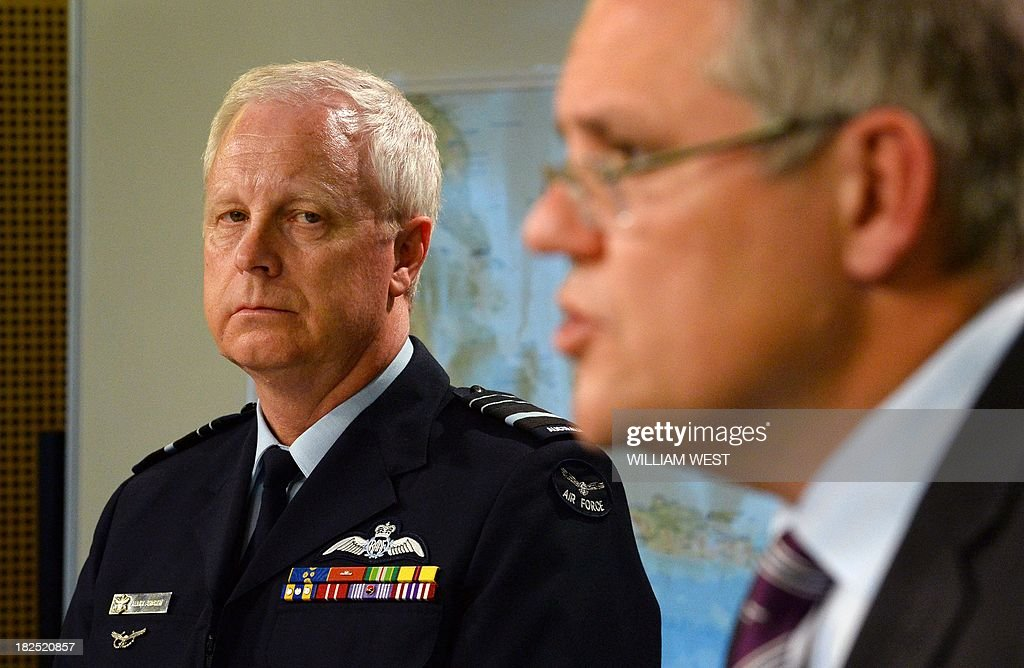 Air Marshal Mark Binskin (L) listens to Australian Immigration Minister Scott Morrison (R) during a press conference in Sydney on September 30, 2013, where Morrison rejected claims that Australian authorities took too long to respond to distress calls from an asylum seeker boat which went down off the coast of Java, killing at least 31 people. Morrison held the second of his weekly briefings on asylum seeker matters as Australian Prime Minister Tony Abbott heads to Jakarta for his first international meeting as Prime Minister, where the boat people issue will high on the agenda of bilateral discussions with his Indonesian counterpart, president Susilo Bambang Yudhoyono. AFP PHOTO/William WEST